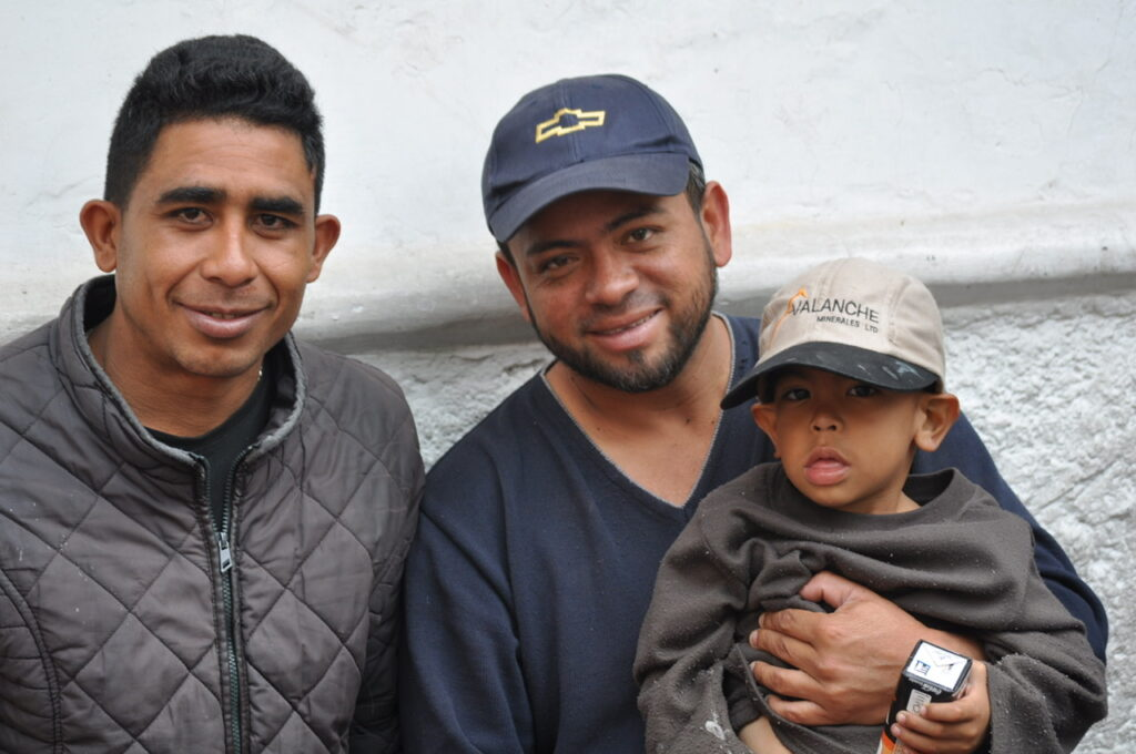 An Ecuadorian father and son sit and enjoy lunch with a friend of the family in Cuenca, Ecuador.